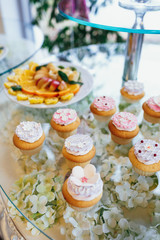 Little cakes with white cream and berries on glass table