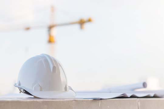 The white safety helmet at construction site with crane background