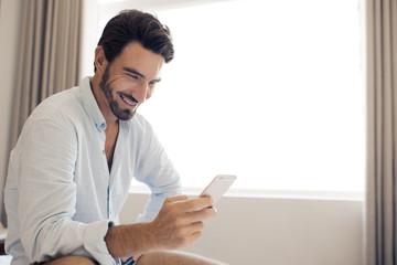 Handsome smiling man using smartphone