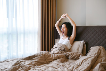 Asian woman yawning and waking up on bed in luxury bedroom in the morning