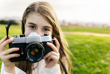 Portrait of a girl holding an old-fashioned camera outdoors