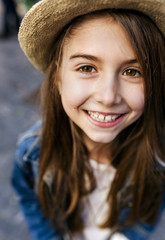 Portrait of a smiling girl wearing a hat outdoors