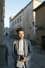 Young tourist man taking pictures with sunset light, Baeza, Spain.