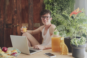 Young man using laptop and drinking orange juice at home