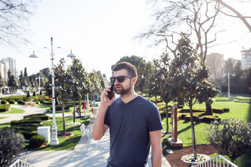 Handsome man with phone at the park.Man talking by phone,man use phone,stylish man in sunglasses using smartphone,casual outfit,stylish hair,attractive,hipster boy with black smartphone,pretty face