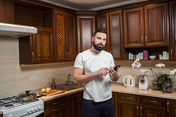 a man in the kitchen talking on the phone