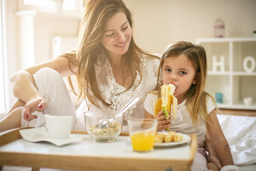 Mother with her little daughter having breakfast in the bed.
