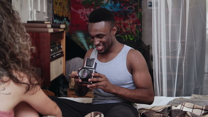 Multiethnic couple on the bed in morning. Young handsome man taking photos on the old photocamera, woman is posing.