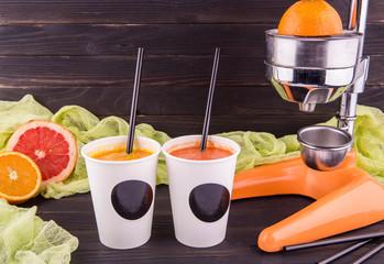 Nonalcoholic juice orange and juice grapefruit in plastic glasses with tubules