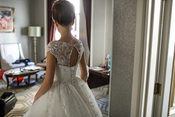 Bride in luxury dress walks around the hotel room