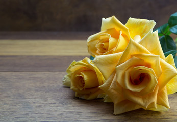 Bright large open yellow roses close up on oak wooden table - background