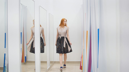 Pretty girl trying dress near mirror in fitting room - shopping concept