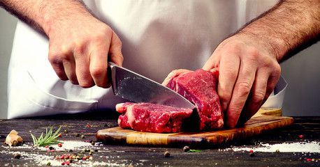 Photo sur Aluminium Viande Man cutting beef meat