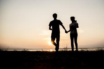 happy couple running on the beach on sunset