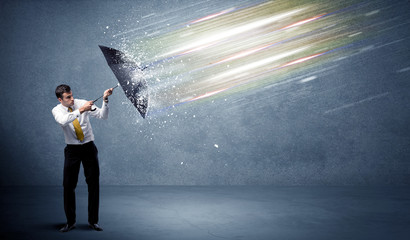 Business man defending light beams with umbrella concept