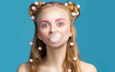 Young funny blond woman with teenage trendy hairstyle blowing pink bubble gum over blue background.