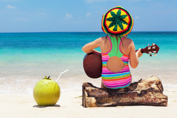 Little happy baby in rastaman hat have fun, play reggae music on Hawaiian guitar, enjoy relaxing on ocean beach. Children healthy lifestyle. Travel, family activity on tropical island summer holiday