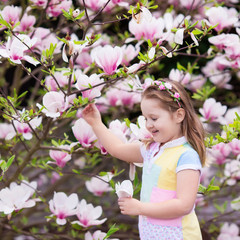Fototapete - Child with magnolia flower. Little girl with flowers
