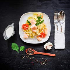 Tasty pasta with salmon and tomato on dark background. Flat lay, top view. Food photo