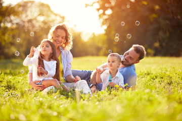 Male and female child blow soap bubbles