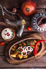 Marinated roasted pork and potatoes with walnuts sauce and wine, Georgian dish ojahuri