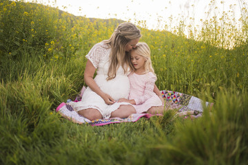 Happy mother kissing daughter on forehead while sitting in park