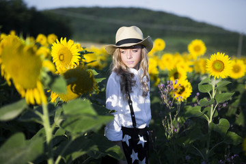 Thoughtful teenage girl in cowboy hat standing on sunflower field during sunny day