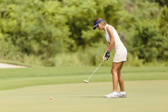 Side view of woman playing golf at golf course