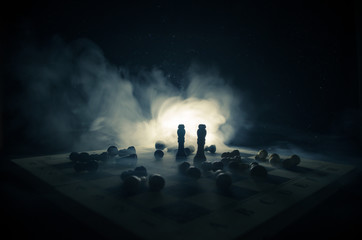 chess board game concept of business ideas and competition and strategy ideas concep. Chess figures on a dark background with smoke and fog.