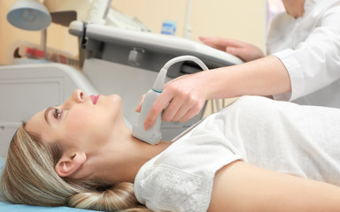 Young woman undergoing ultrasound scan in modern clinic