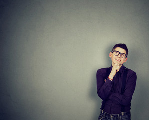 Young happy man leaning on a wall looking up thinking