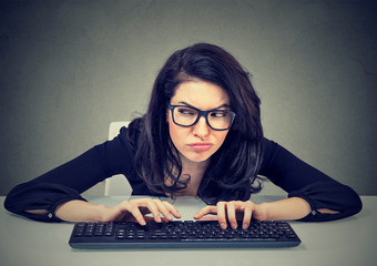 Crazy looking nerdy woman typing on the keyboard plotting a revenge