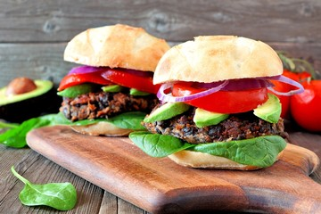 Veggie bean and sweet potato burgers with avocado and spinach against a rustic wooden background