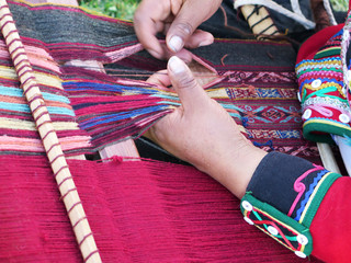 Close up of Peruvian lady in authentic dress spinning yarn by hand