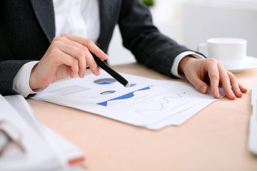 Business woman sitting at the table and examines the financial results