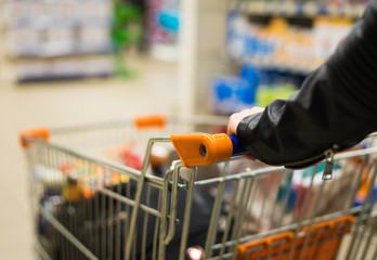 Abstract photo of woman carrying a cart or trolley in the supermarket.