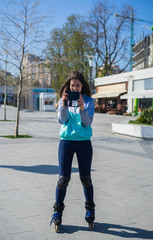 Beautiful Roller Girl standing and taking selfie on smartphone. Sunny day.