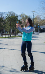 Beautiful Roller Girl standing and shooting selfie on smartphone
