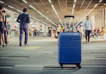 Suitcases in airport departure terminal with traveler people walking in background,Holiday vacation concept, Business trip,selective focus on suitcases