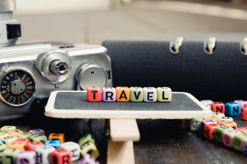 conceptual image with TRAVEL word block on wooden signage over soft focus background