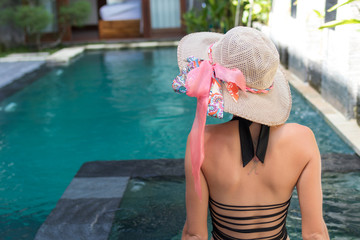 Young woman in swimsuit in swimming pool in gorgeous resort, luxury villa, tropical Bali island, Indonesia.