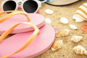 pink flipflops, sunglasses, and seashells on beach sands