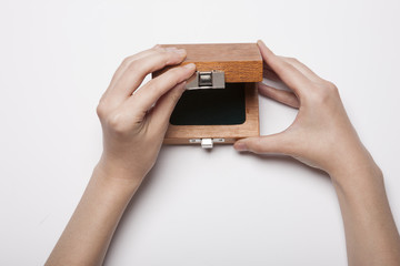 woman hand hold a wood case(package) isolated white.