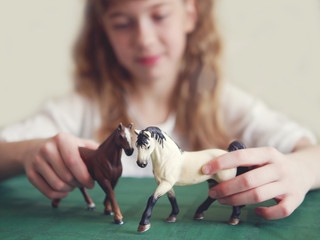 The girl is playing with the figures of horses.