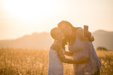 Happy mother and daughter taking selfie by smartphone outdoors