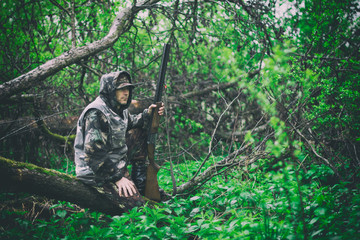 A man hunter with a gun sits on a fallen tree in rainy weather in a spring forest, toned photo