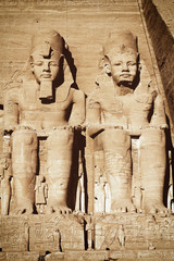 The Abu Simbel temple. View of the statues represent Ramesses II and his wife Nefertari. Edited as a vintage photo with dark edges.