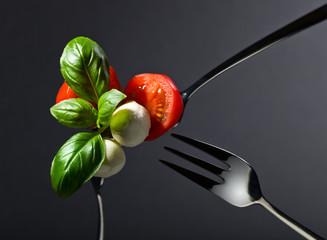 Mini mozzarella with tomato cherry and green basil .