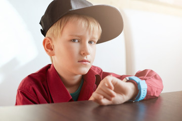 A horoizontal portrait of serious male child wearing trendy cap and red shirt having a smart watch on his wrist sitting at wooden table over white background. A handsome little boy with watch.