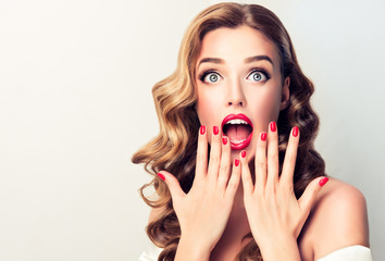 Shocked and surprised girl screaming covering  mouth her hands . Woman amazed .Beautiful girl  with curly hair and red nails manicure. Presenting your product..Expressive facial expressions